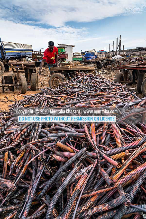 Agbogbloshie in September 2020: Photo of an urban poor man arranging copper materials from recycled heliax coaxial cables. The wires had been burned in the open just by the Korle Lagoon. Copyright © 2020 Muntaka Chasant