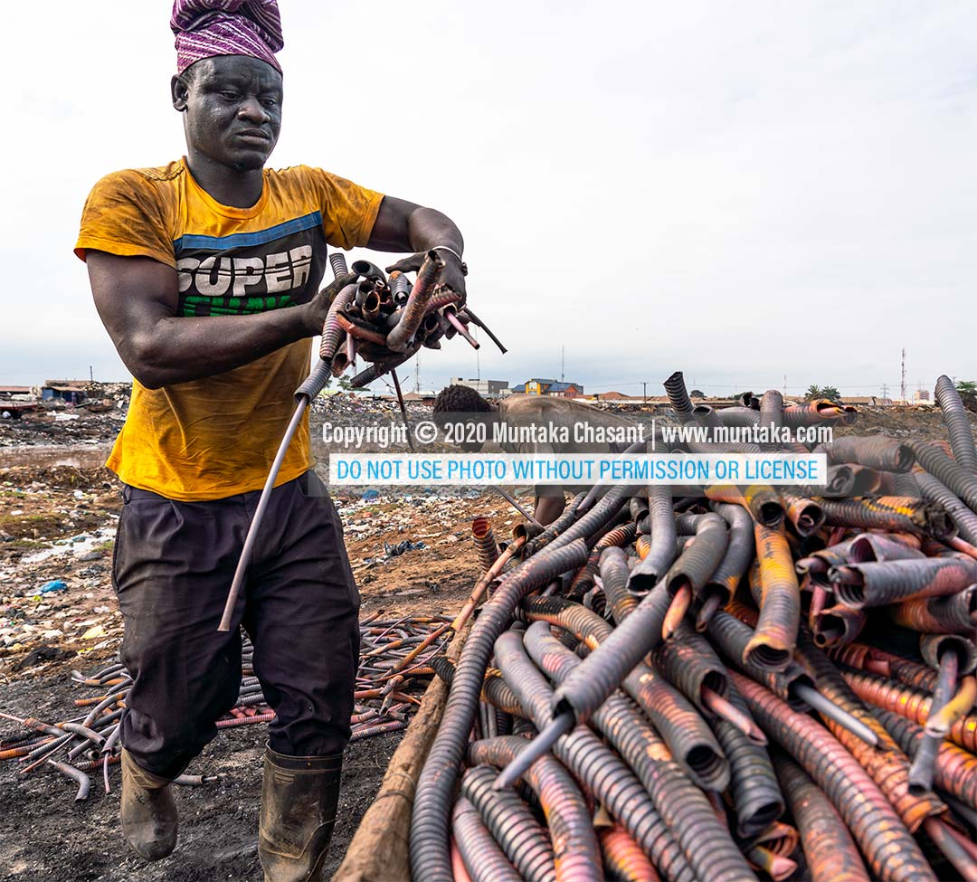 Recycling heliax cable at Agbogbloshie: Man is arranging copper materials from burned heliax coaxial cables to be carted away. Copyright © 2020 Muntaka Chasant