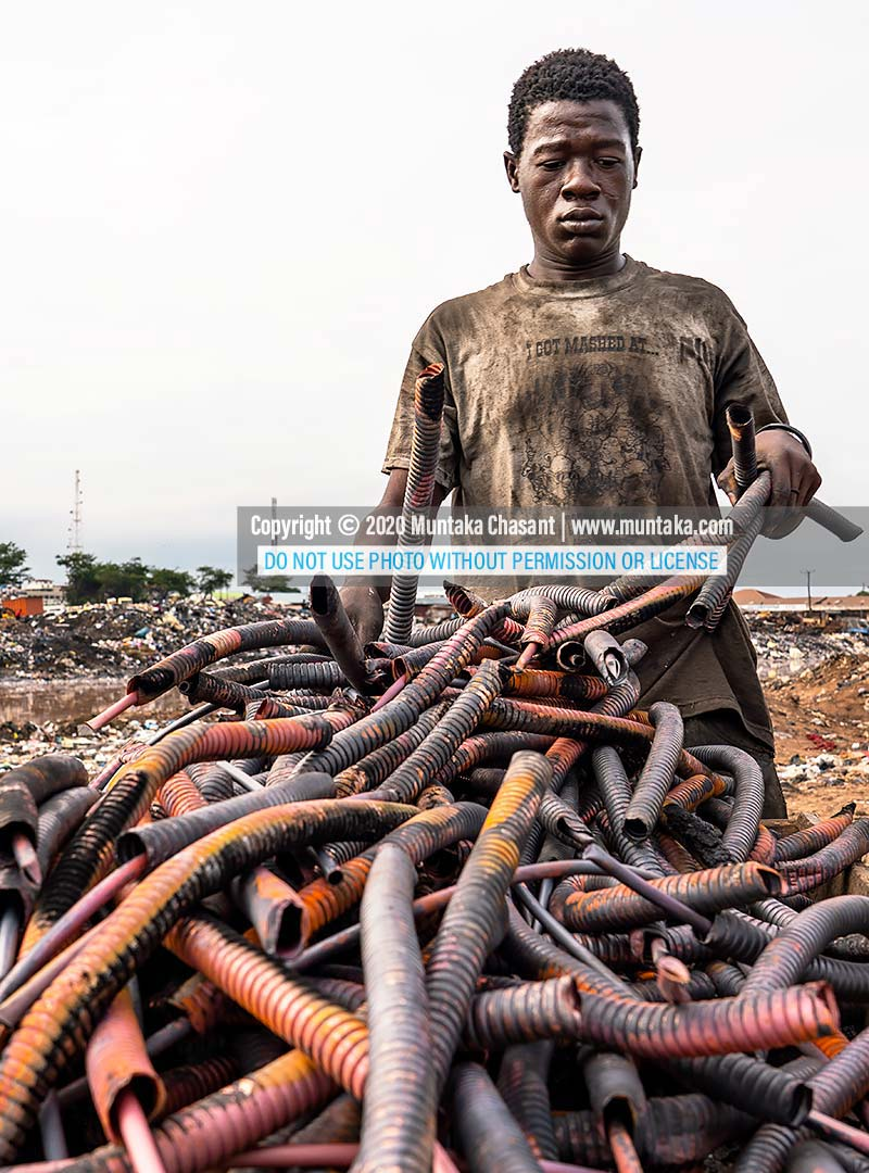 Agbogbloshie: Urban poor man arranges copper from recycled heliax coaxial cables at Agbogbloshie, Ghana. Copyright © 2020 Muntaka Chasant.