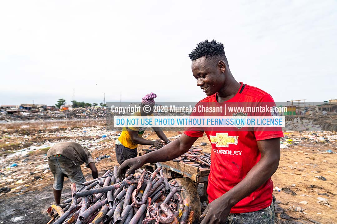 Agbogbloshie: Nicknamed 'Zongo boy,' urban poor man is happy they have copper from recycled heliax cables. 'Zongo boy' is a local musician. Copyright © 2020 Muntaka Chasant