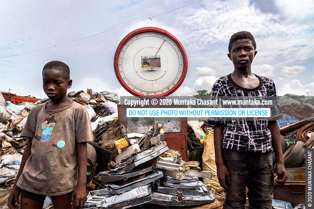 Child labour in Ghana: Mustafa, 13 years, and Osei, 15, are weighing shadow masks, and other iron materials from old CRT TVs they had used bare hands and stones to dismantle. Iron scraps sold for around $0.15 per kilo at Agbgobloshie in May 2020. Nearly 2 million children in Ghana are in child labour, according to UNICEF. © 2020 Muntaka Chasant
