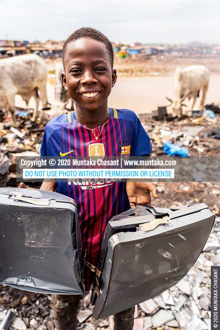 Child Labour: Kweku Frimpong, 12 years old, smile and display shadow masks he had just reclaimed from old CRT TVs at Agbogbloshie, Ghana. © 2020 Muntaka Chasant