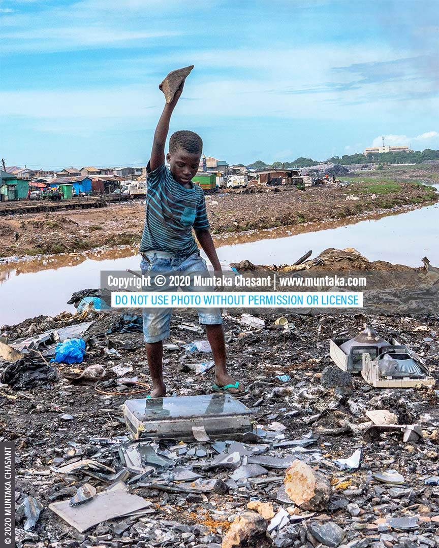 Child poverty in Ghana: 11-year-old Ibrahim is using a stone to break apart an old CRT TV to reclaim the precious metals inside at Agbogbloshie, Ghana. Nearly 2 million children in Ghana aged 5 - 17 years are in child labour. © 2020 Muntaka Chasant