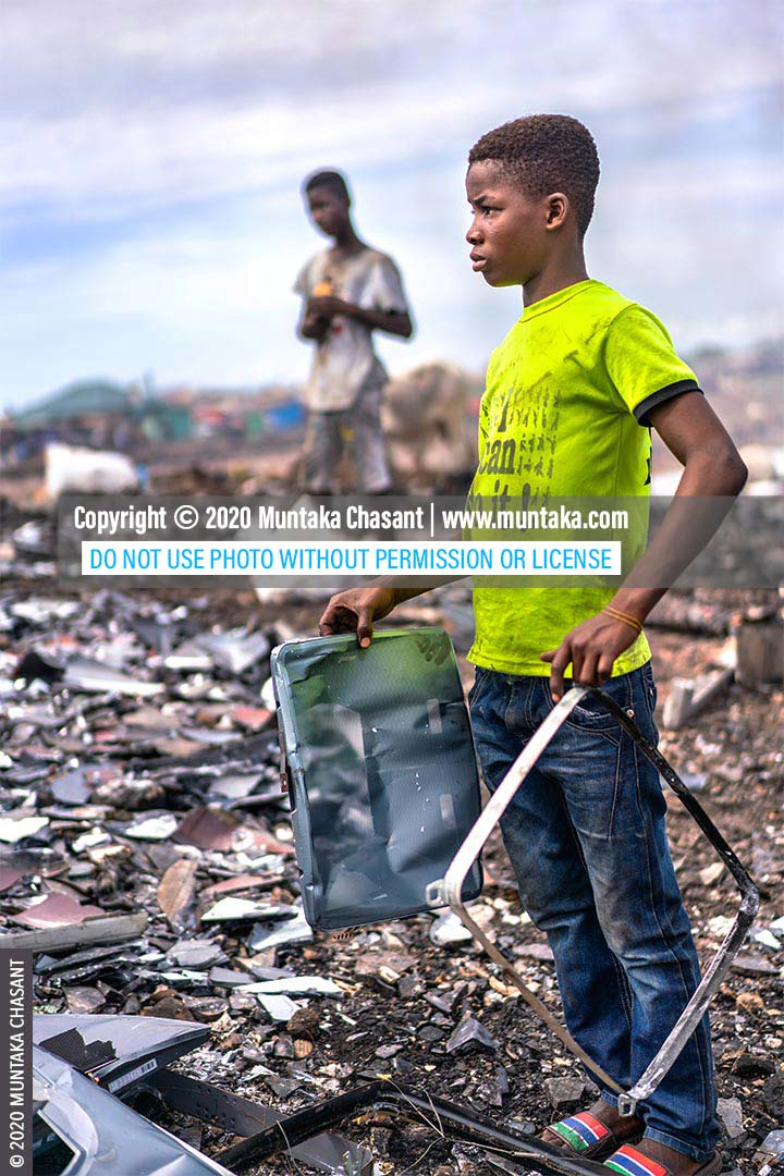 Electronic waste recycling and child labour: 14-year-old Bright Ankrah has recovered iron materials from an old CRT TV at Agbogbloshie, Ghana. These sold for $0.15 per kilo in May 2020. Approximately 14% of children in Ghana between 5 and 17 years in hazardous child labour, UNICEF estimates show. © 2020 Muntaka Chasant