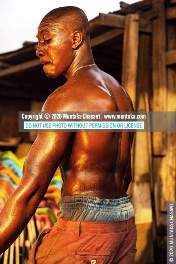 Hard working man: A semi-naked man is sweating working near a fire in the early morning light. Thousands of young people in Ghana flee rural poverty to cities in search of economic opportunities every year. With no education, many of them turn to the informal sector, where some of them engage in hazardous works. © 2020 Muntaka Chasant