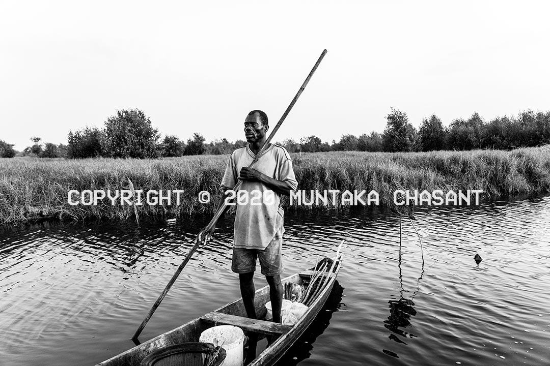 Urban poor fisherman in a wooden canoe on a creek near salt marsh and tidal mangrove forest. Accra, Ghana. Copyright © 2020 Muntaka Chasant