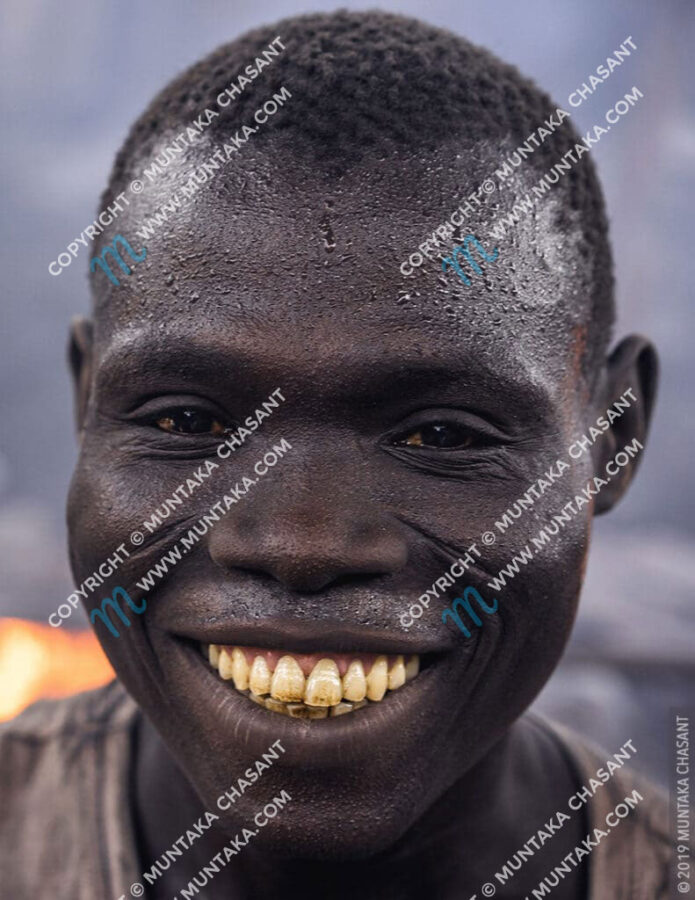 Man Smiling Photo: Poor hard-working African man smiling at the camera. © 2019 Muntaka Chasant