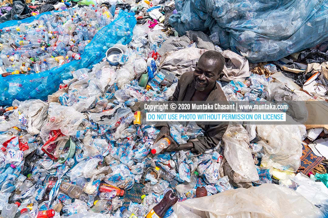 Urban poor African man: An urban poor old African man in Accra, Ghana, sits on a mat in a dumpsite to separate and organize recyclable waste plastics. Copyright © 2020 Muntaka Chasant