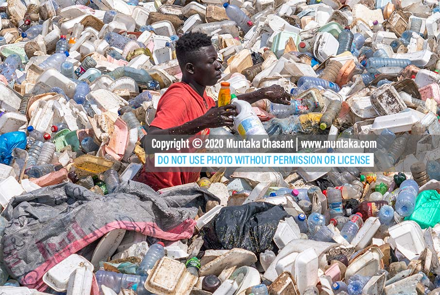 Urban poor man swims in the polluted Korle Lagoon in Accra, Ghana, to recover recyclable plastics. Plastic pollution is visible in many African countries, where municipal waste management systems are inefficient. Copyright © 2020 Muntaka Chasant