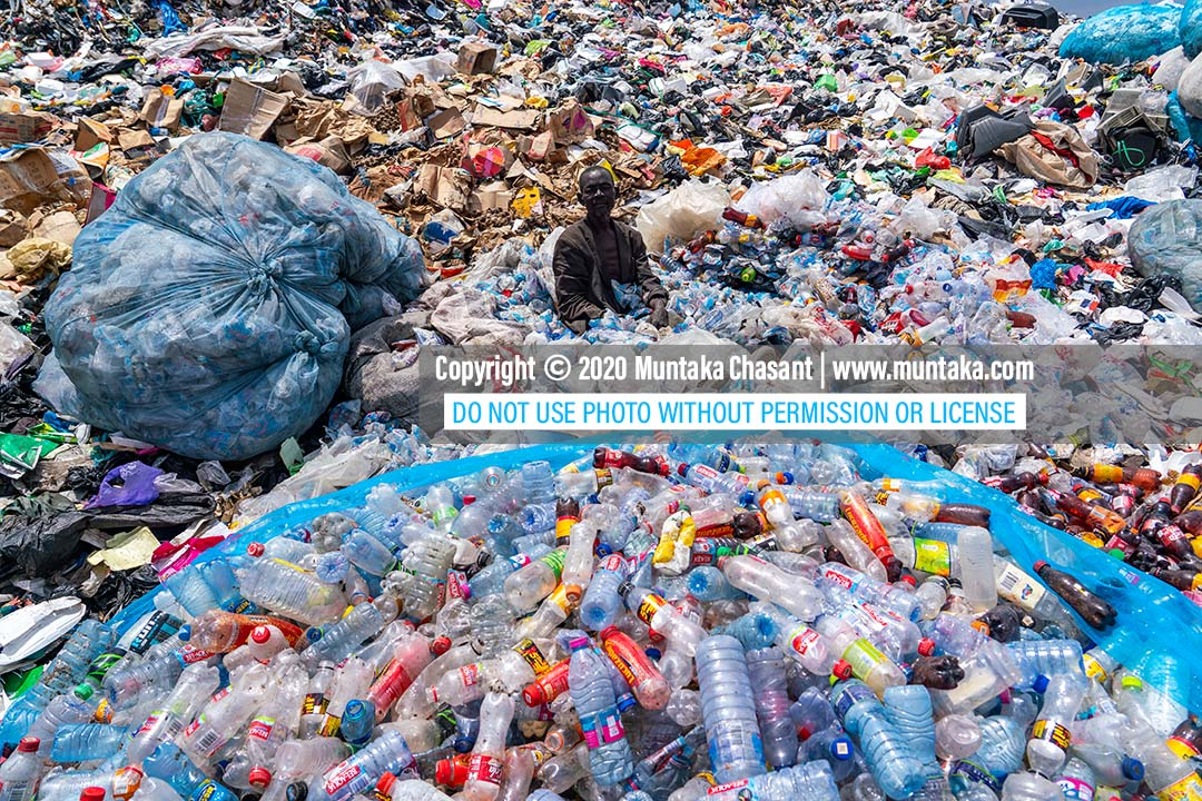 Plastic pollution in Ghana: Urban poor man sorts recyclable plastics at a dumpsite in Accra, Ghana's capital city. September 2020. Copyright © 2020 Muntaka Chasant