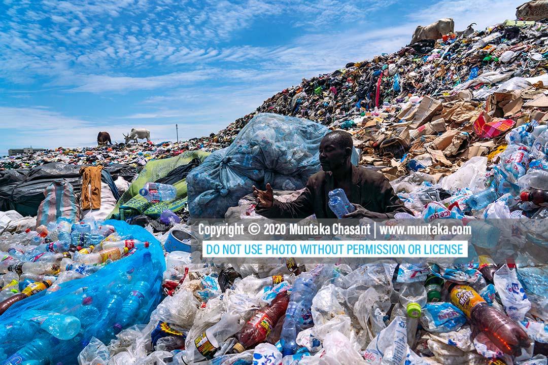 Plastic pollution photo: Elderly poor African man sorts waste plastics at a dump in Accra, Ghana. Copyright © 2020 Muntaka Chasant