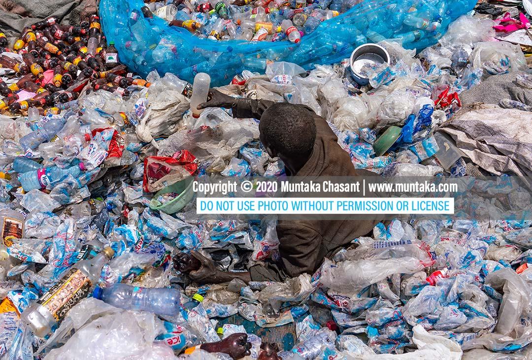 Plastic waste in Ghana: Urban poor elderly African man sorts recyclable plastics at a dumpsite in Accra, Ghana. Copyright © 2020 Muntaka Chasant