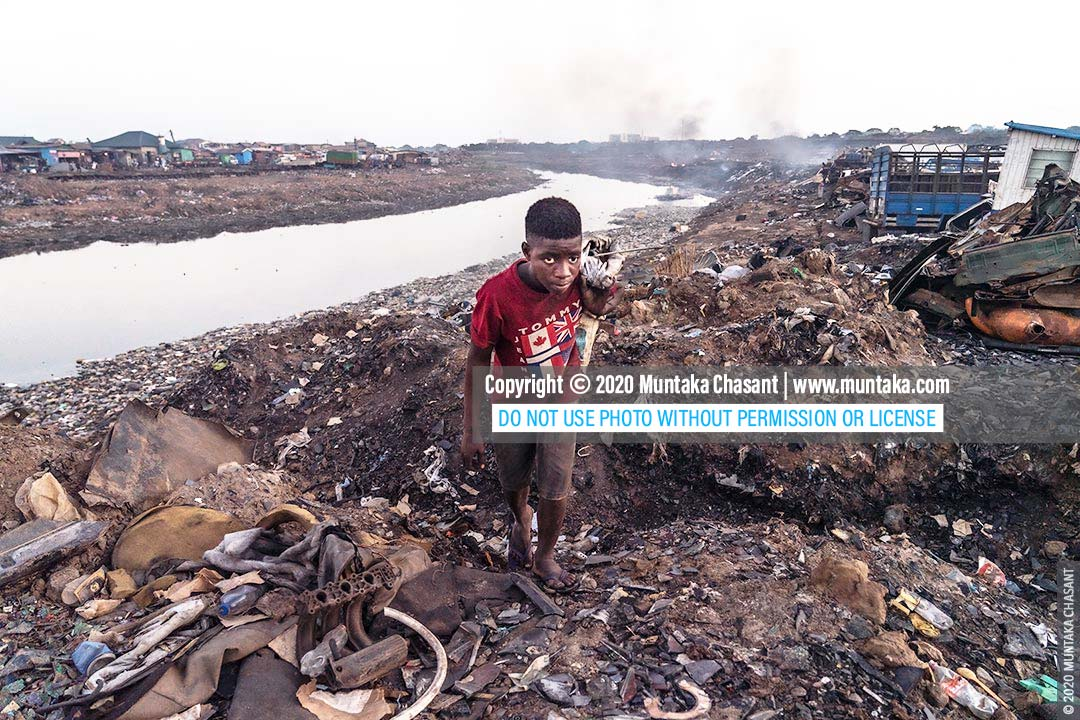 Urban Poverty: 15-year-old Debrah is an urban poor engaged in hazardous child labour. He scavenges for scrap metals on the fringes of Agbogbloshie, Ghana. © 2020 Muntaka Chasant