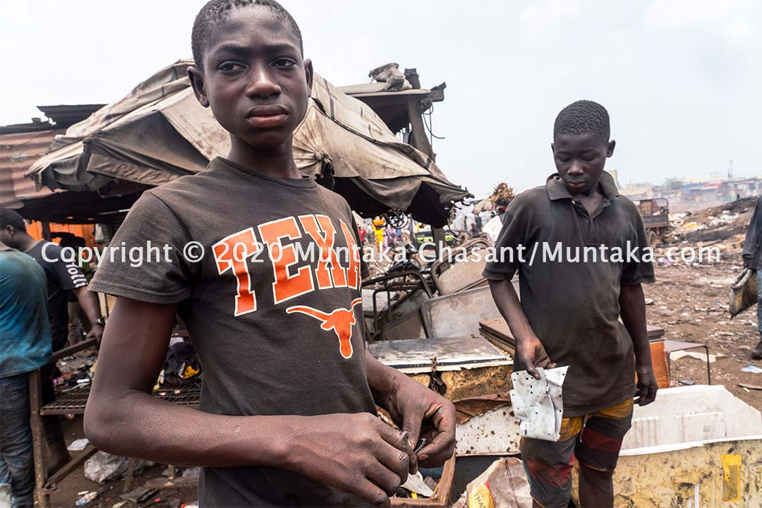 Child labour at Agbogbloshie: Benjamin Duodu, 14 years, and Joseph Akwah, 17, at Agbogbloshie cannibalizing from discarded e-waste. Despite being badly cut by metal, Duodo still used his fingers to sift through the soil to retrieve metals. Copyright © 2020 Muntaka Chasant
