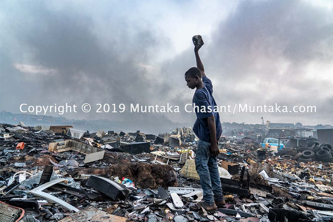 Agbogbloshie: Benjamin Duodu, 13 years old, use a rock to break apart old cathode-ray tube TV glass for the iron materials inside. Copyright © 2019 Muntaka Chasant
