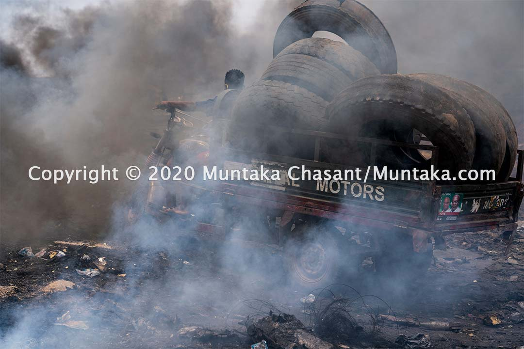 Agbogbloshie: Man about to pull up to unload a bunch of scrap tires. Scrap workers at Agbogbloshie burn scrap tires in the open for steel wires. Copyright © 2020 Muntaka Chasant