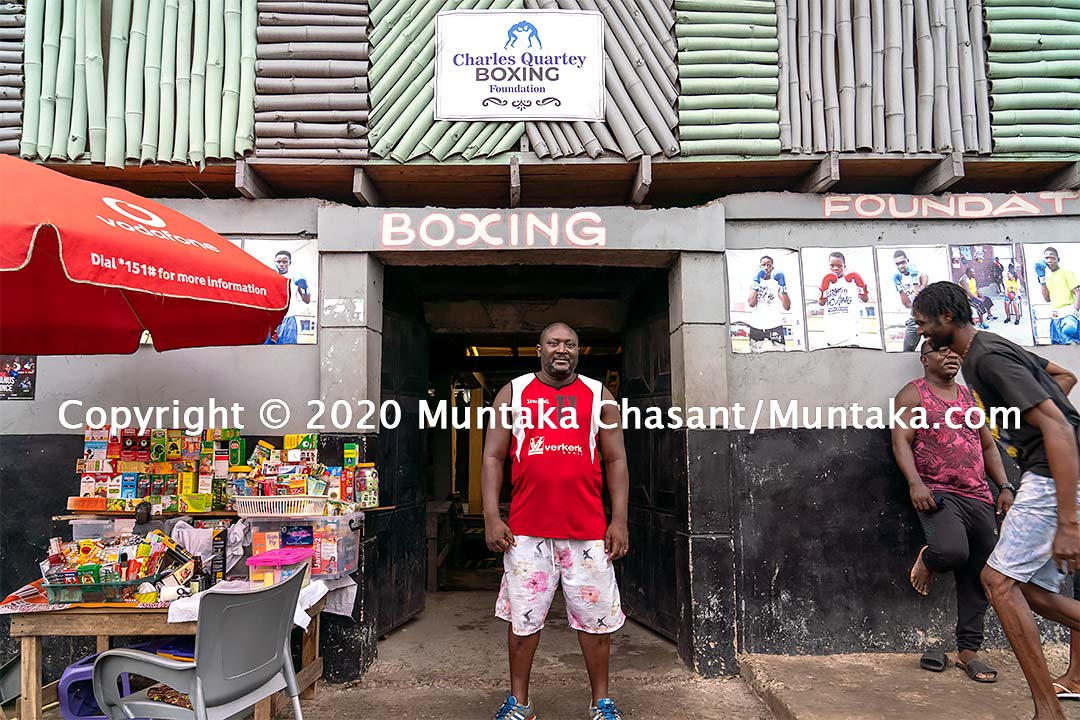 Charles Quartey stands in front of the Charles Quartey Boxing Foundation near the Sodom and Gomorrah slum in Accra, Ghana. Copyright © 2020 Muntaka Chasant