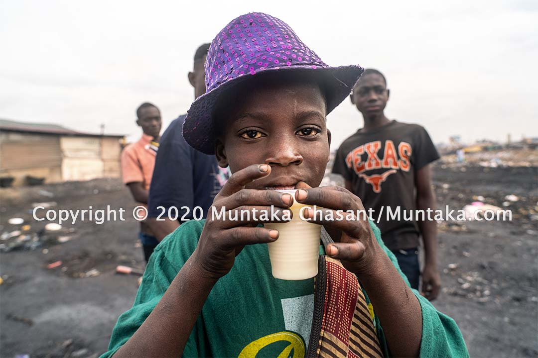 Child labour in Ghana: 11-year-old Tanko is having breakfast before going out to use his bare hands to sift through the soil to recover scrap metals — in an area renowned for its heavy metals pollution. Copyright © 2020 Muntaka Chasant