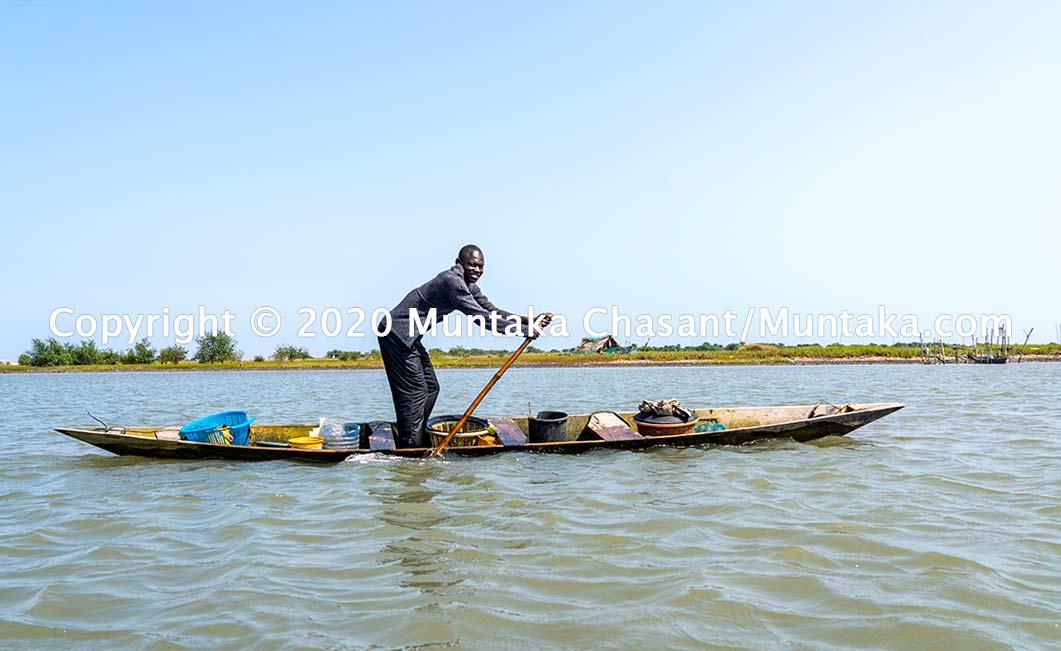 Fisherman paddling a canoe. Copyright © 2020 Muntaka Chasant