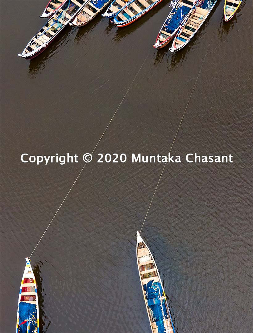 Fishing in Ghana: 10 anchored canoes in Ghana. Copyright © 2020 Muntaka Chasant