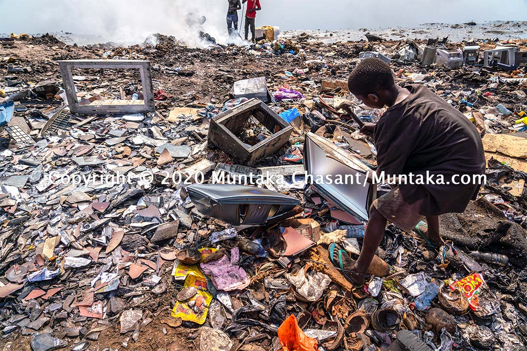 Hazardous child labour: A 12-year-old boy uses a hammer to dismantle an old CRT TV to recover the iron materials inside. Agbogbloshie, Ghana. Copyright © 2020 Muntaka Chasant