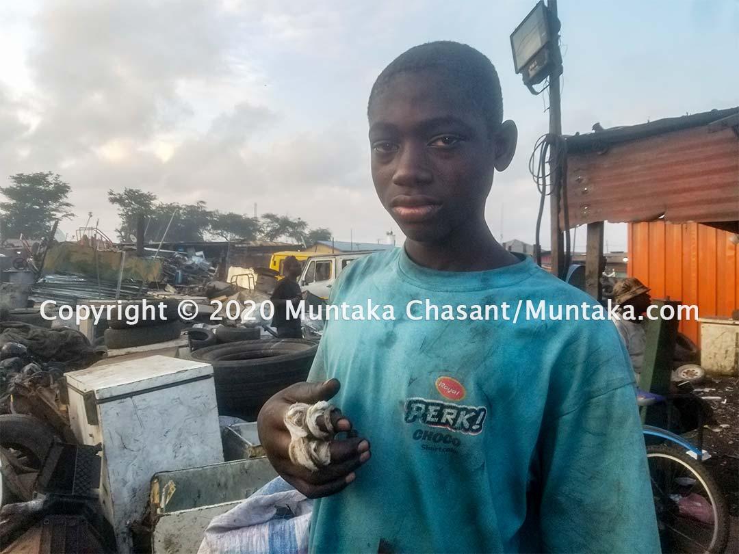 Benjamin Duodu, 14 years old, in pain after being cut by scrap metal. Agbogbloshie, Ghana. Copyright © 2020 Muntaka Chasant