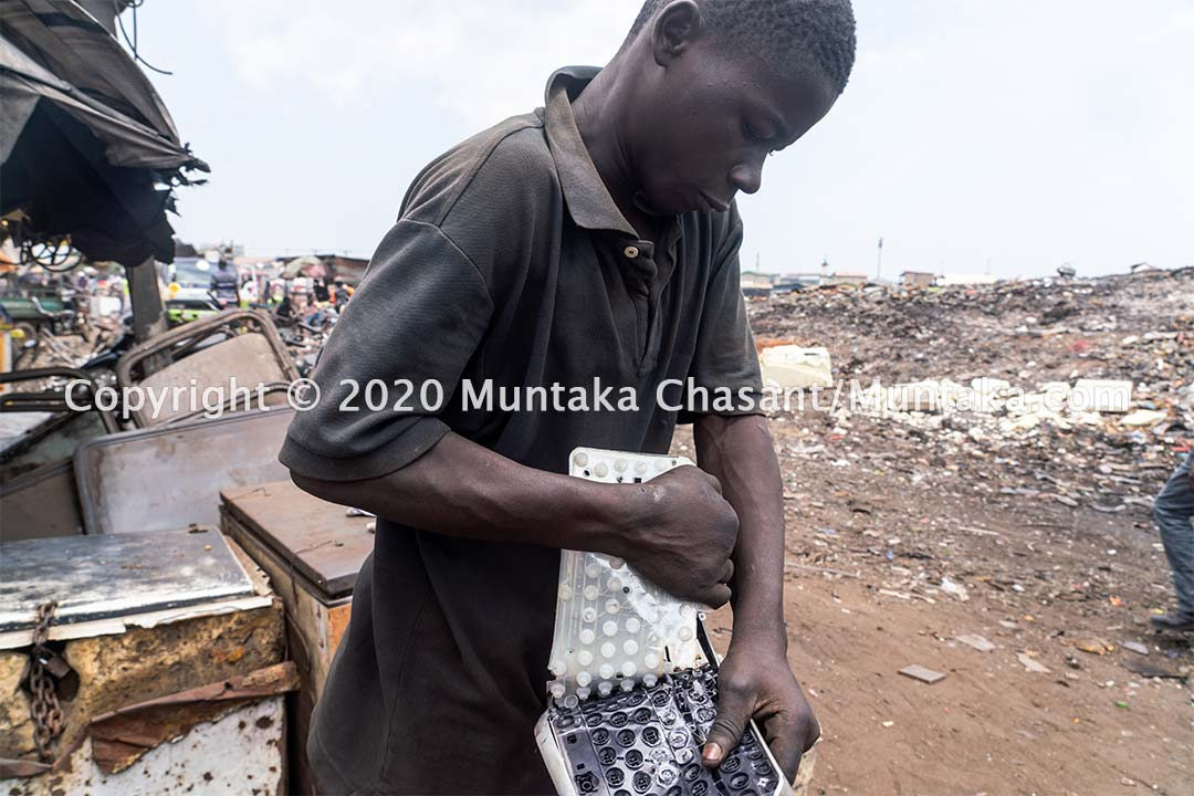 A 17 years old E-waste worker manually dismantles a computer keyboard for scrap metal at Agbogbloshie, Ghana. Copyright © 2020 Muntaka Chasant