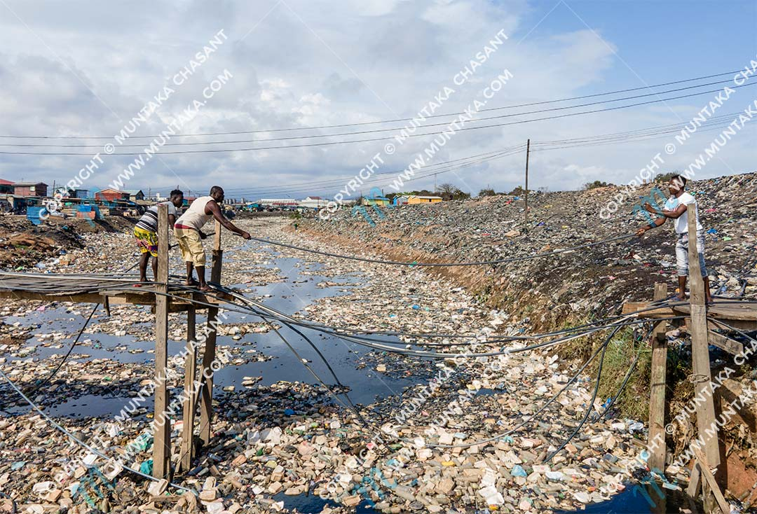 Men reconnect water pipes and fix broken wooden bridge at the Sodom and Gomorrah slum near the center of Accra, Ghana. Copyright © 2020 Muntaka Chasant