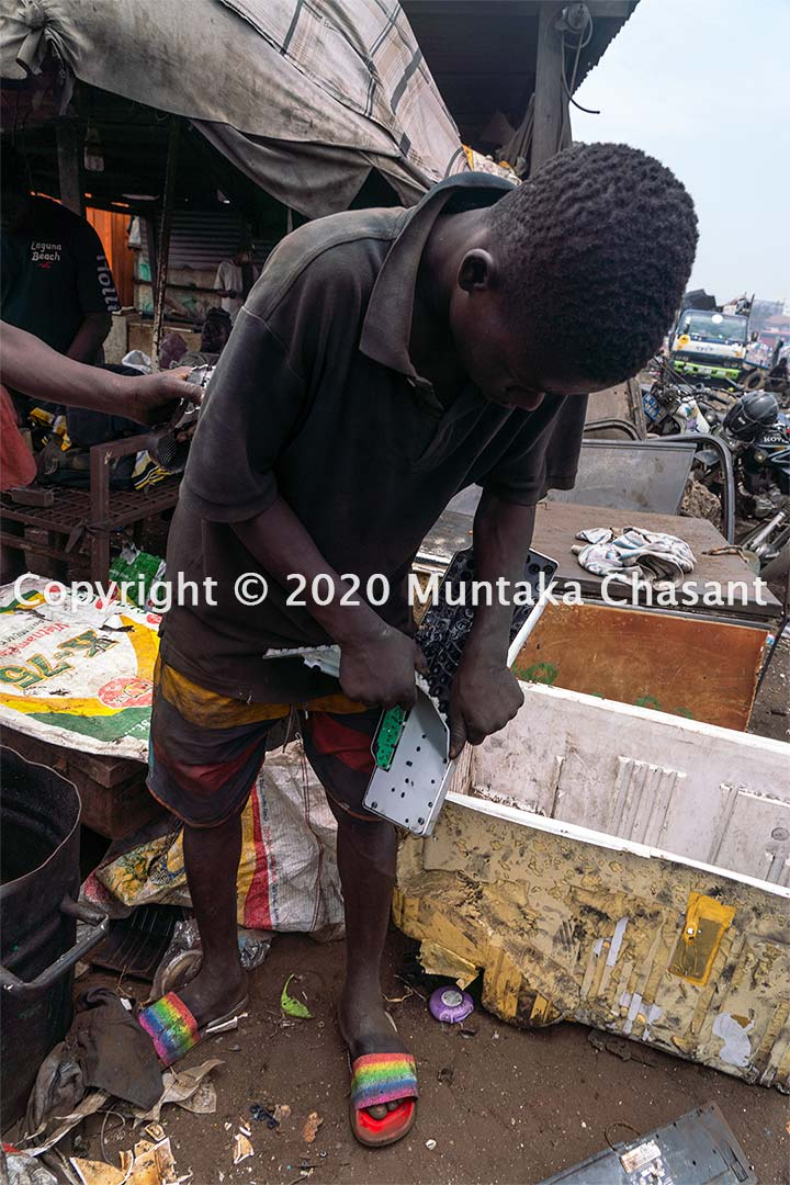 Urban poor adolescent boy manually dismantles a computer keyboard at Agbogbloshie in Accra, Ghana. Copyright © 2020 Muntaka Chasant