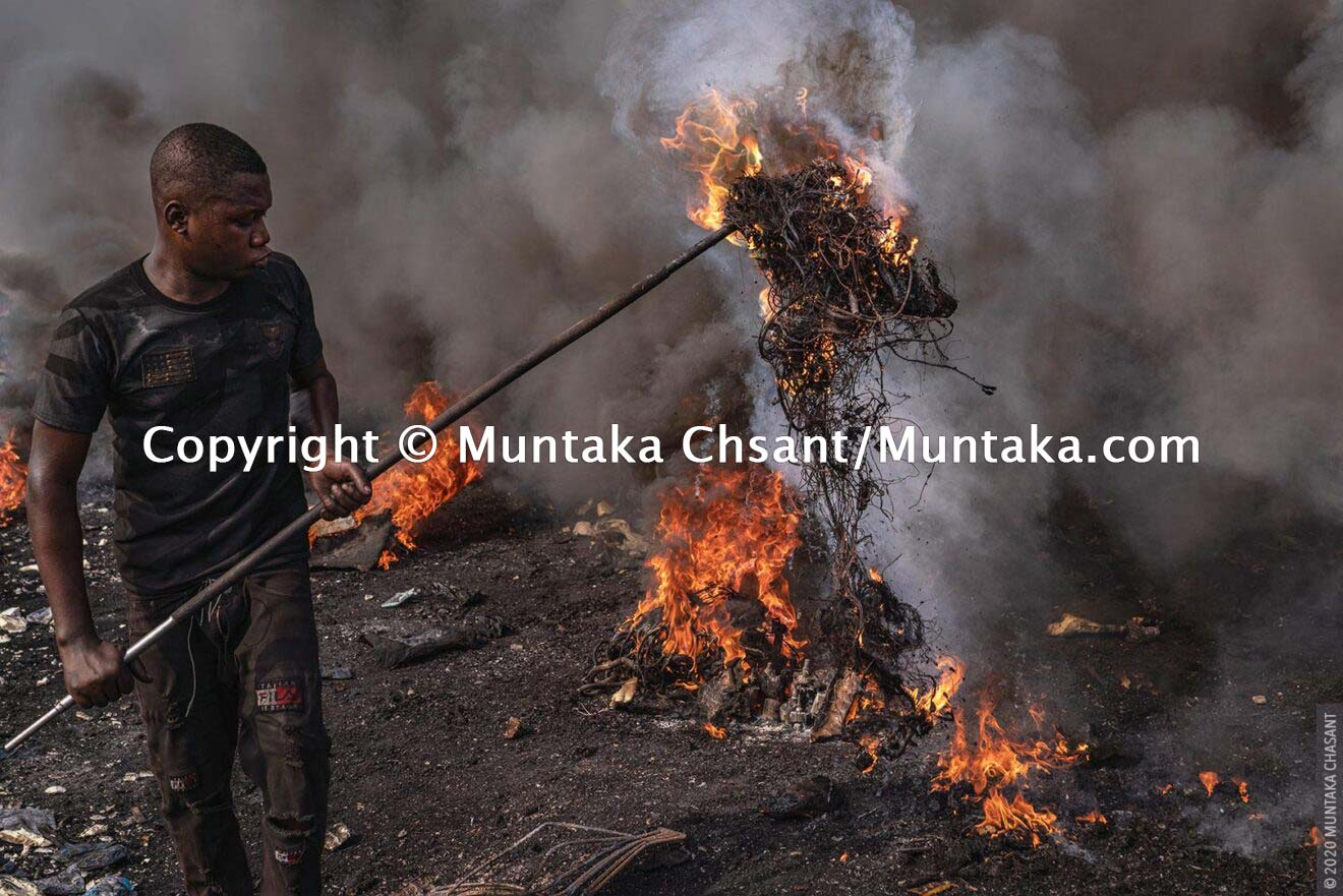 A 'burner boy' burning electrical wires to recover the copper material inside at Agbogbloshie, Ghana. © 2020 Muntaka Chasant