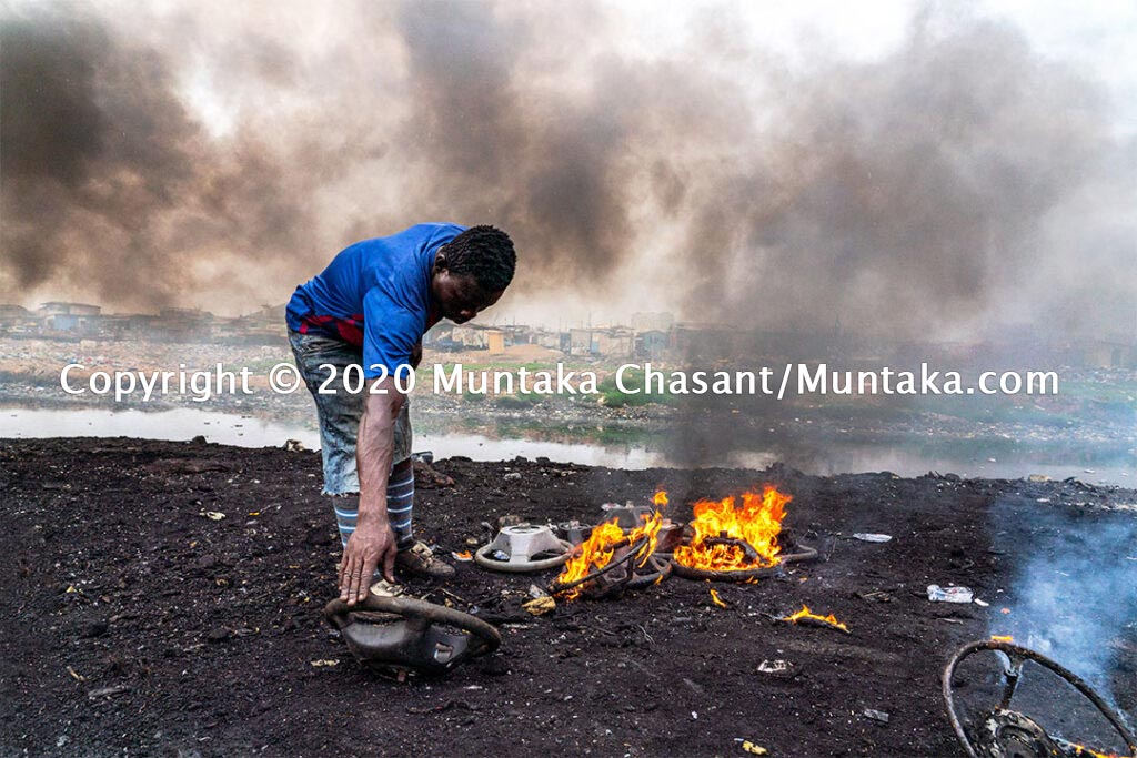 Informal recycling at Agbogbloshie: Man is openly incinerating car steering wheels to reclaim the aluminium materials inside. Decades of primitive and informal e-waste and auto parts recycling at Agbogbloshie have contaminated the soil, groundwater, and Accra's air. © 2020 Muntaka Chasant