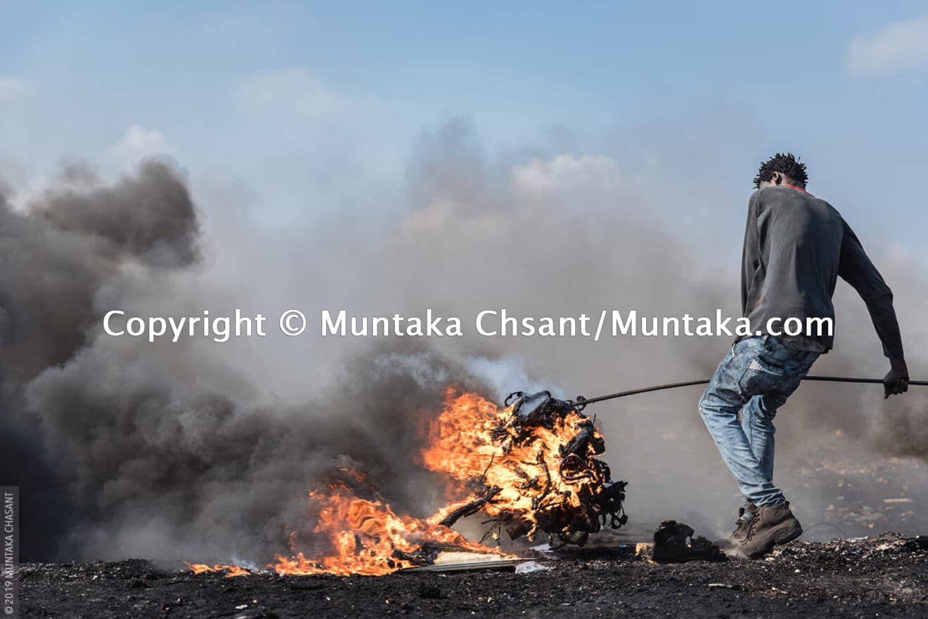 Man is burning electrical wires to recover the copper inside at Agbogbloshie, Ghana. © 2019 Muntaka Chasant