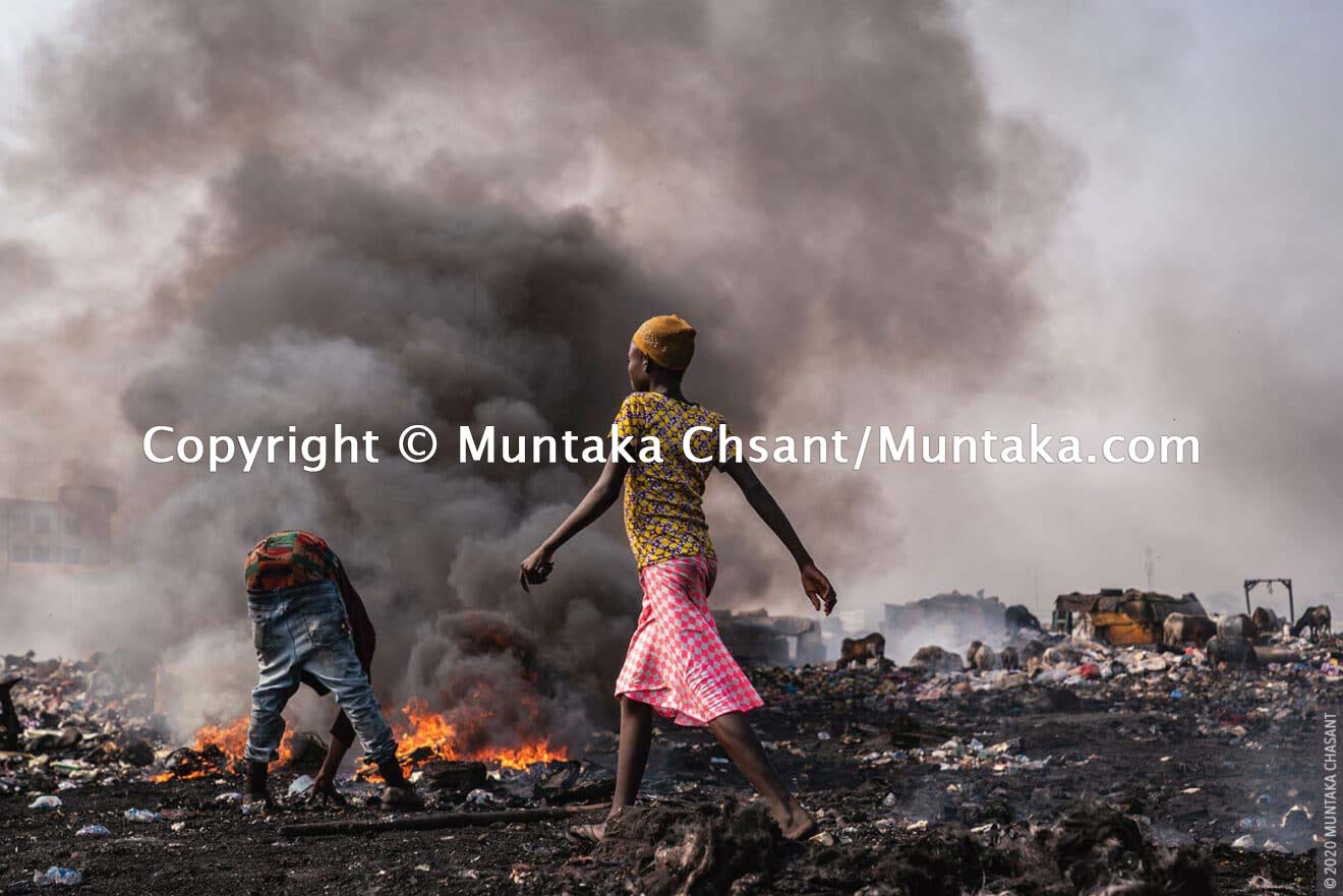 A young woman walk passes the smoking fires of burning electrical wires at Agbogbloshie. 'Burner boys' use styrofoam packing and scrap tires as fuel to openly burn insulated wires to recover the copper materials inside at Agbogbloshie, Ghana. © 2020 Muntaka Chasant