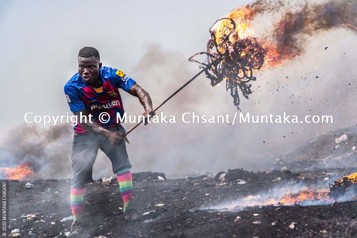 Awal is an 'experienced' burner boy. He is burning electrical wires to recover the copper materials inside at Agbogbloshie, Ghana. The reclaimed copper are carted away and sold for instant cash. © 2020 Muntaka Chasant