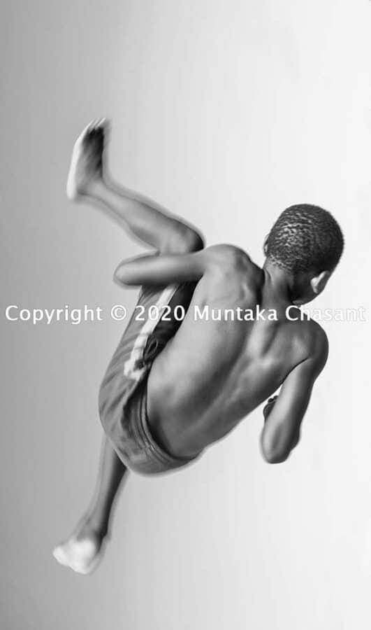Children playing: Boy doing a backflip. Copyright © 2020 Muntaka Chasant