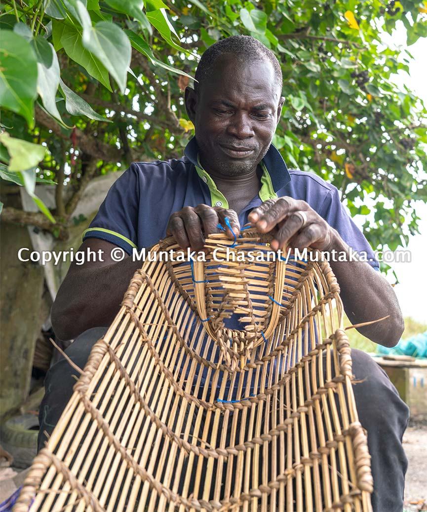 Fisherman in Ghana hand making a blue crab trap. Copyright © Muntaka Chasant