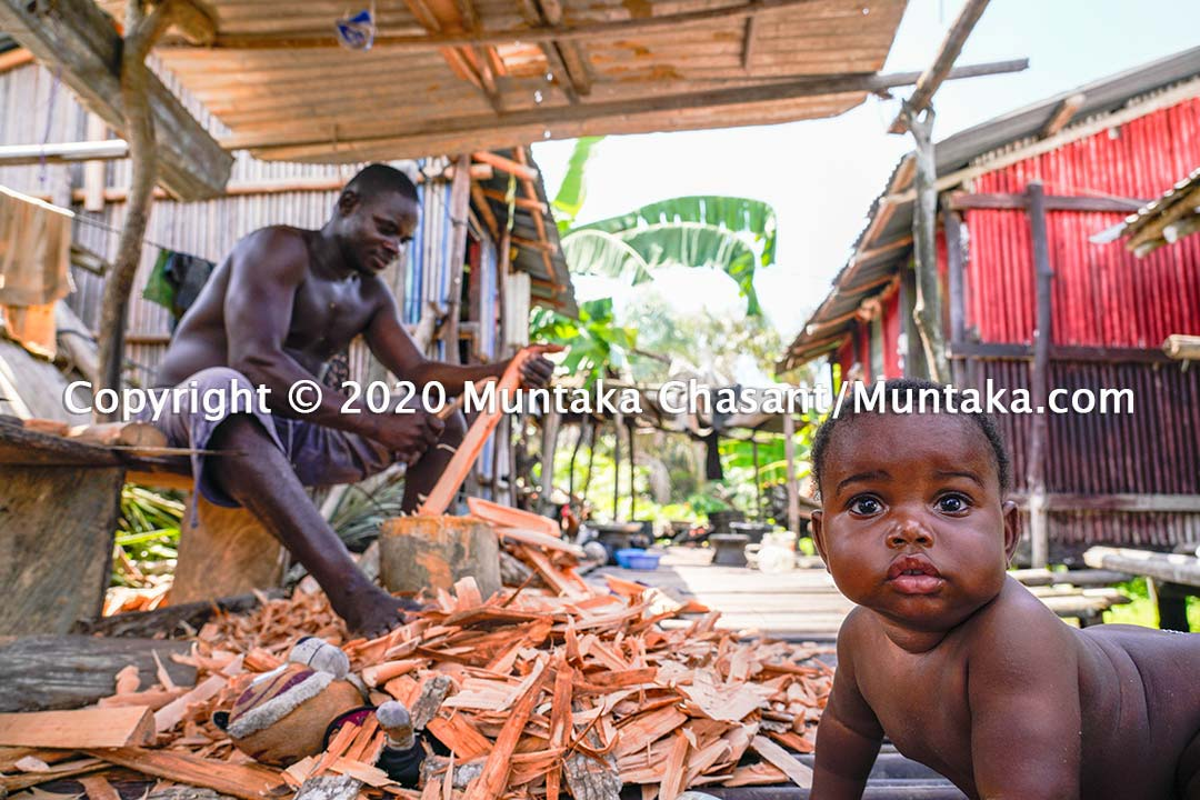 Nzulezo, Ghana: Working with his son playing nearby, the artisan in the background relies on tourist traffic to his stilt village to sell his crafts to feed his family. But low traffic due to the coronavirus pandemic puts his livelihood at risk. Copyright © 2020 Muntaka Chasant