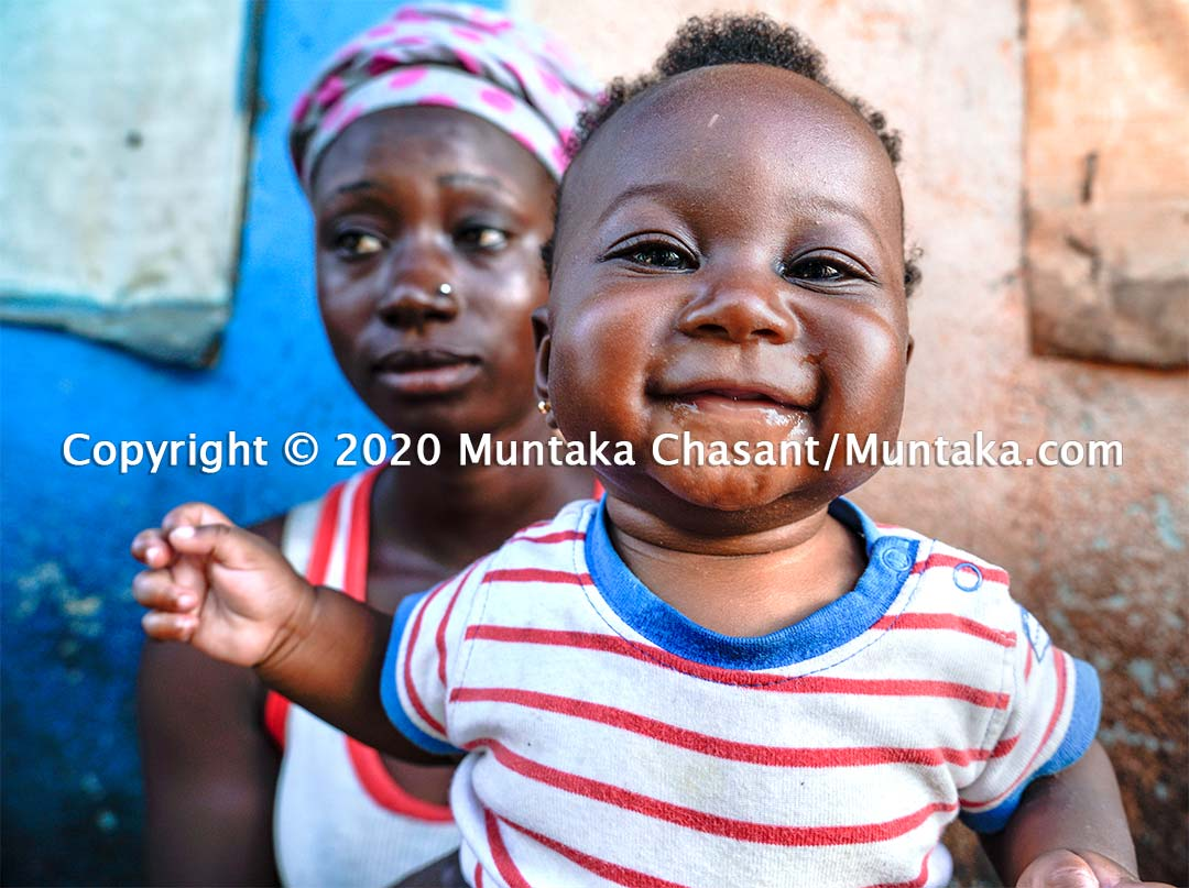 Childhood innocence: An infant smiles against her hopeless urban poor mother. Copyright © 2020 Muntaka Chasant
