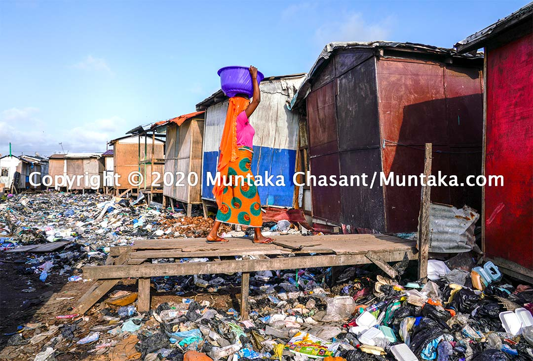 Sodom and Gomorrah, Ghana: Urban poor woman carries water on her head as she makes her way across a wooden bridge in a rubbish-strewn environment. Copyright © 2020 Muntaka Chasant