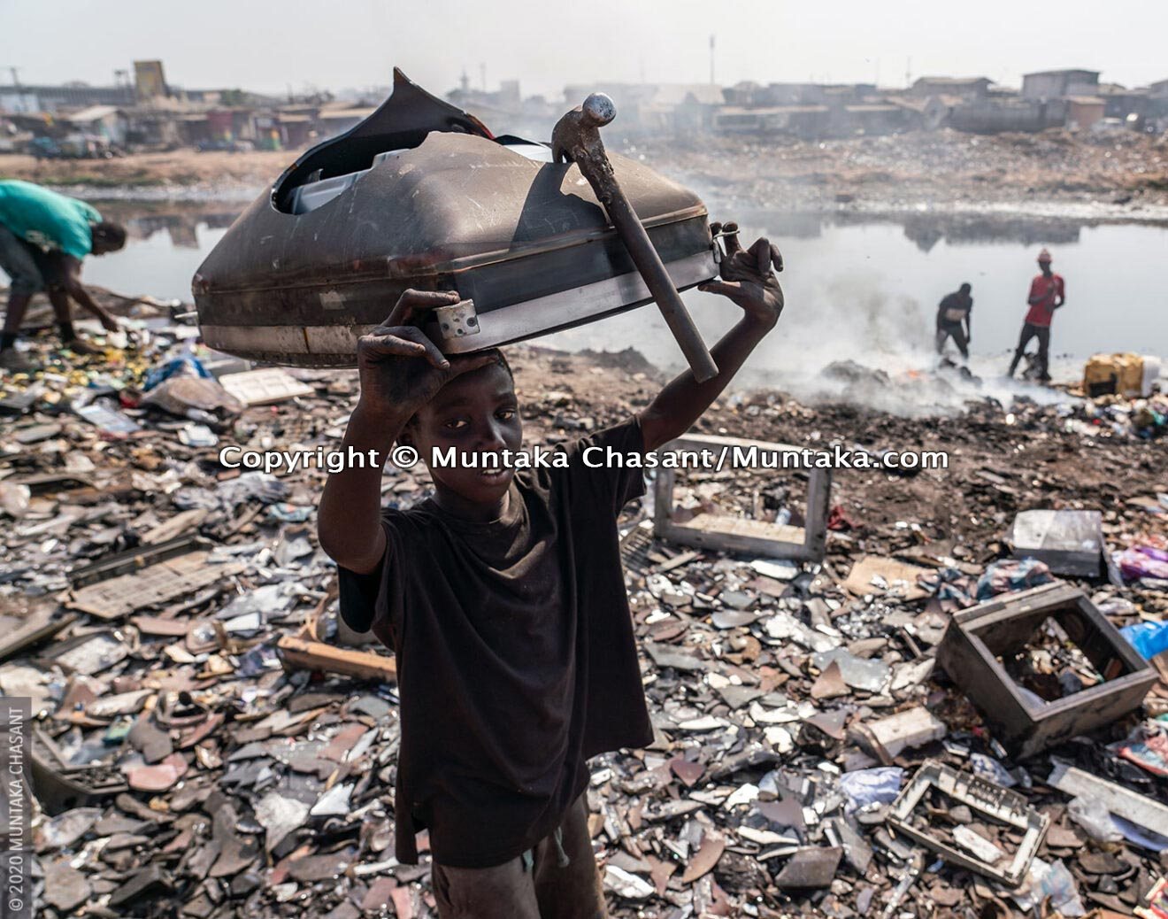 Hazardous child labour: A 12 years old boy carries a cathode-ray tube-based TV on the head. He used a hammer to break it apart for the iron materials inside. An estimated 152 children worldwide between 5 and 17 years are in child labour. © 2020 Muntaka Chasant