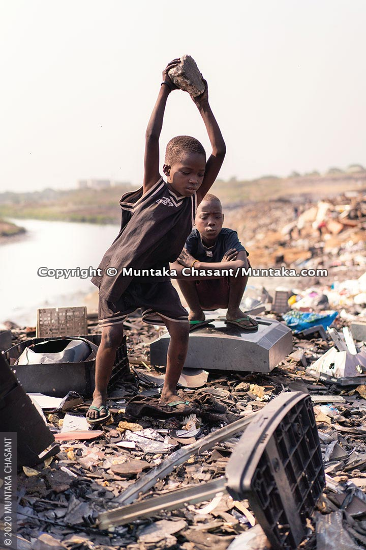 Hazardous child labour: Kwadwo is a 9 years old boy engaged in hazardous child labour at Agbogbloshie, Ghana. In the photo, he is using a stone to break apart a cathode-ray tube-based television for the iron materials inside. This exposed him to dangerous levels of lead. © 2020 Muntaka Chasant