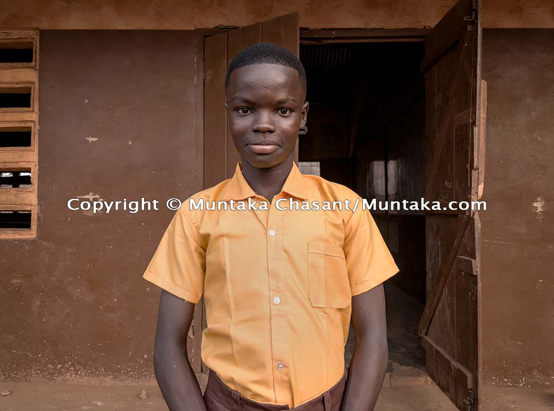 Kingsford Sarfo, 14 years, in front of his classroom (grade 3) on his first day at the Ashia Mills Basic School in Accra, Ghana's capital city. Kingsford had been engaged in hazardous child labour around the Agbogbloshie area since 2014 when his parents had him brought to the area. Copyright © 2021 Muntaka Chasant
