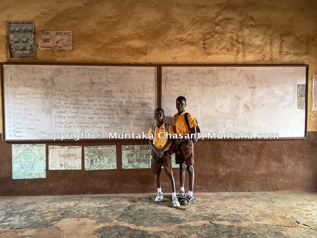 Natus and Kingsford on their first day at school inside class 3 (grade 3) of the Ashia Mills Basic School near the center of Accra. Copyright @ 2021 Muntaka Chasant
