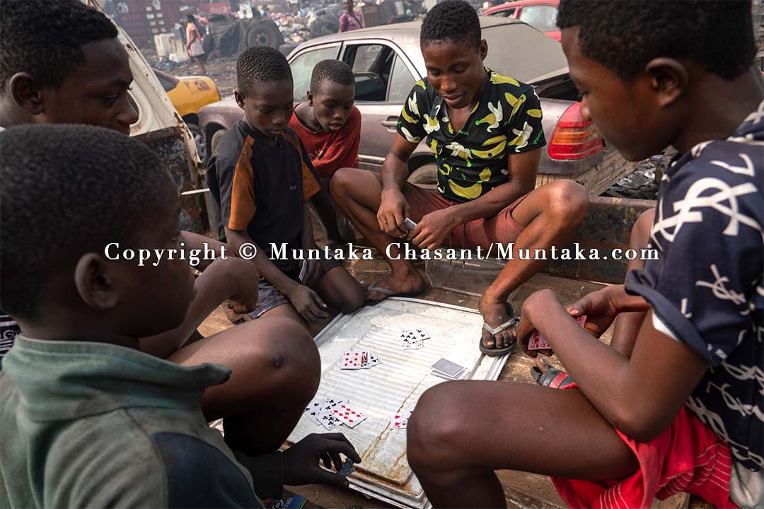 Young people engaged in hazardous child labour play cards. Copyright © 2021 Muntaka Chasant