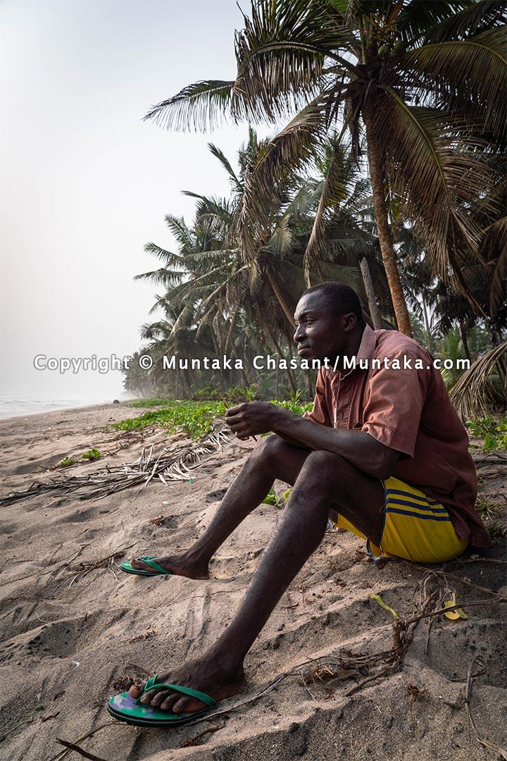 Simon rests on the undisturbed rural beach. Copyright © 2021 Muntaka Chasant