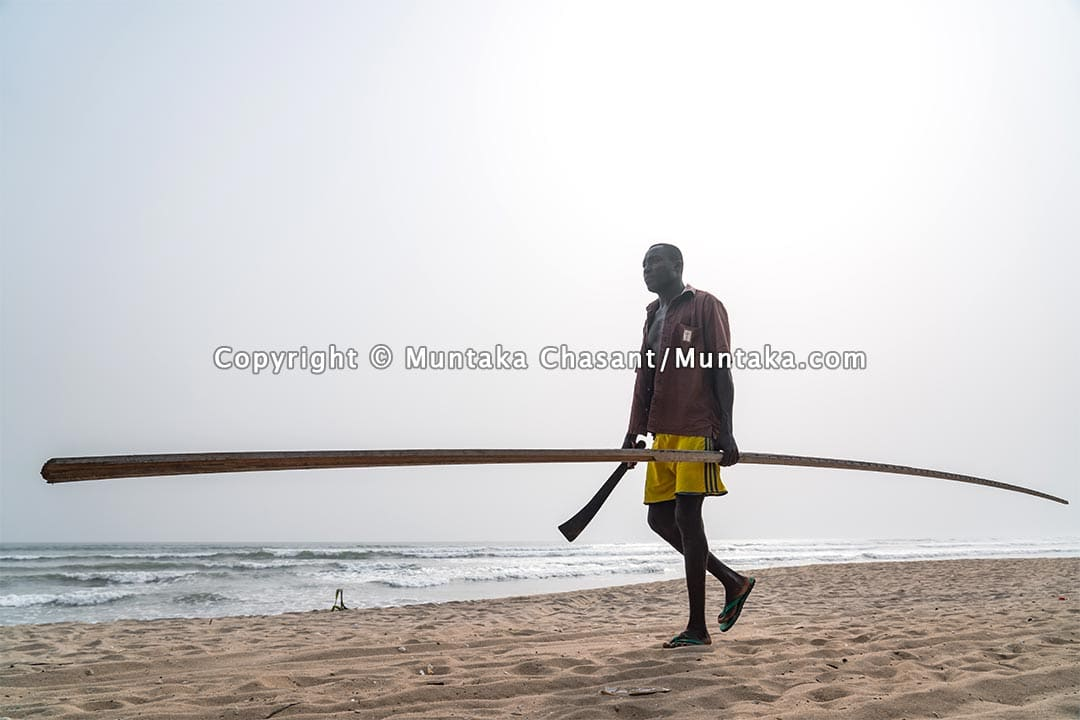 Man walks on the beach holding cutlass and a long stick. Copyright © 2021 Muntaka Chasant