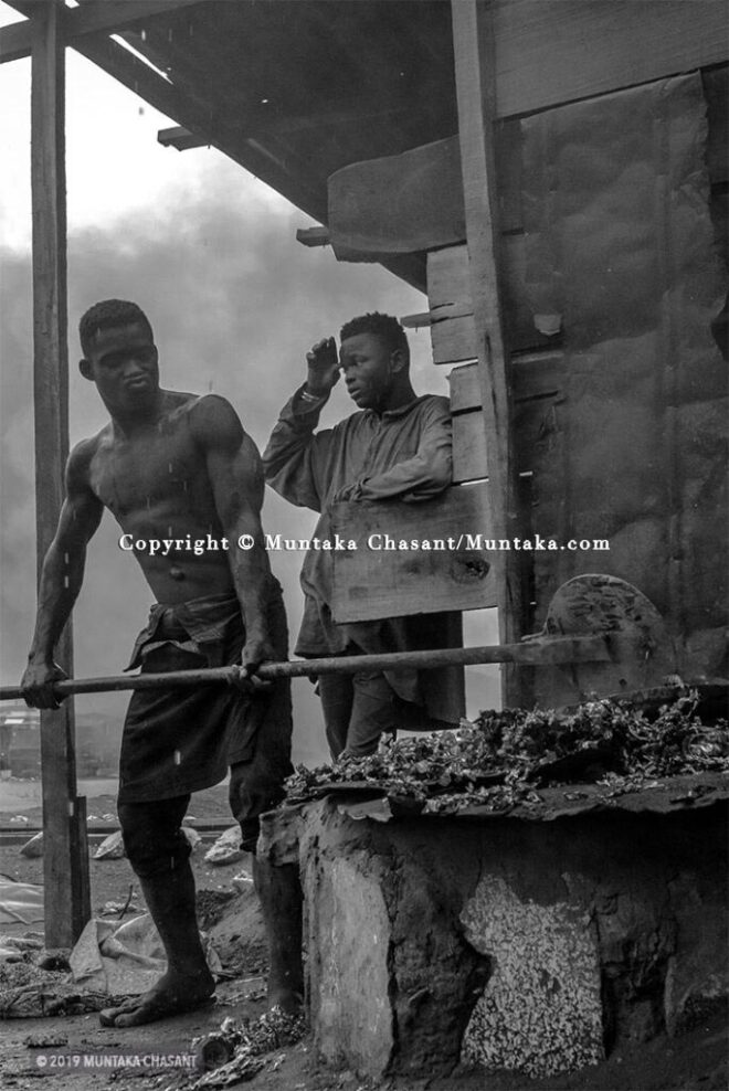 #half In The Rain: A man uses open-pit fires to melt AC condensers fins into molten metal. © 2019 Muntaka Chasant