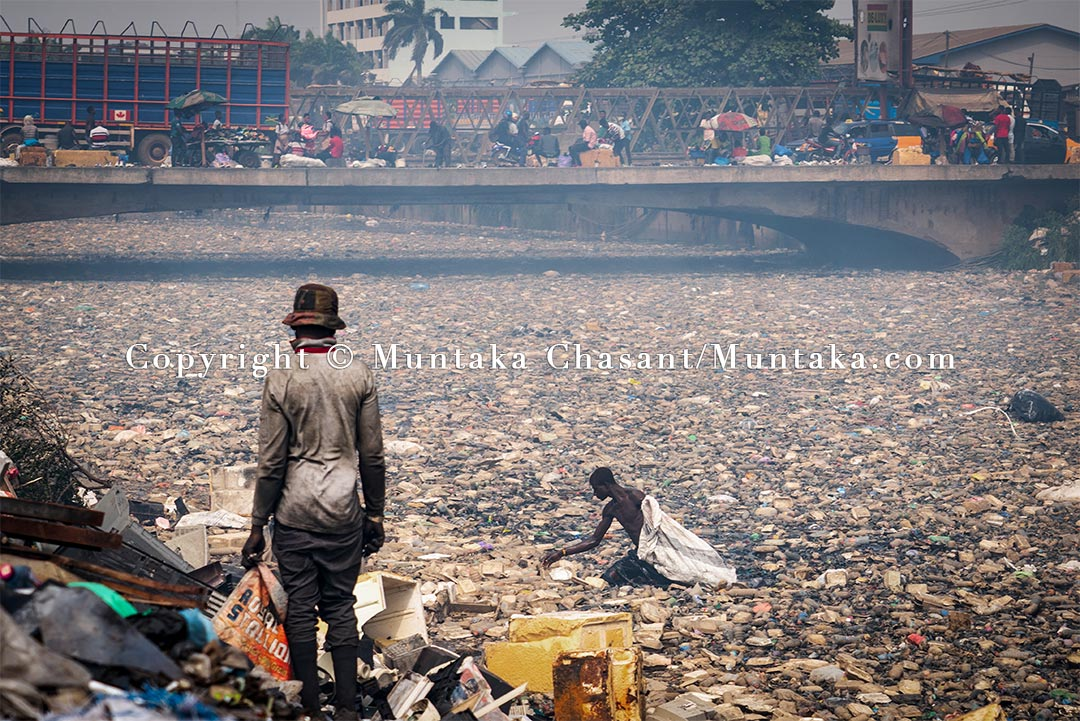 A young Ghanaian man swims in the polluted Korle Lagoon to recover recyclable plastics and cans. Copyright © 2021 Muntaka Chasant