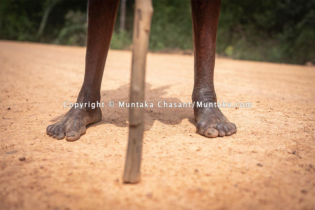An elderly rural poor woman from the farm walks barefooted on a dirt road. Ghana. Copyright © 2021 Muntaka Chasant