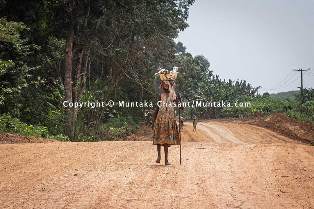Elderly rural poor woman from the farm walks barefooted on a dirt road in rural Ghana. Copyright © 2021 Copyright © 2021 Muntaka Chasant